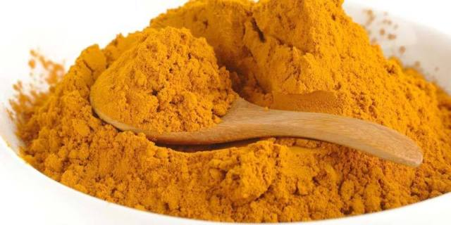 curcumin turmeric powder with wooden spoon